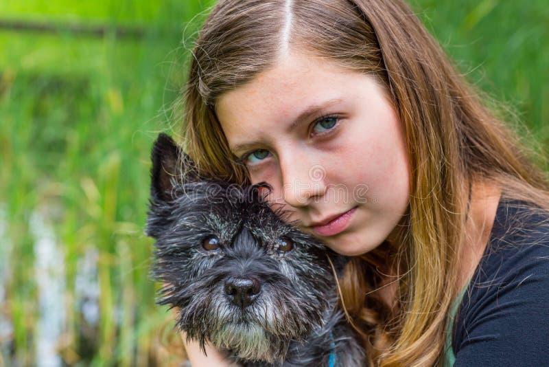 Ragazza bionda che abbraccia e che abbraccia cane nero immagini stock libere da diritti