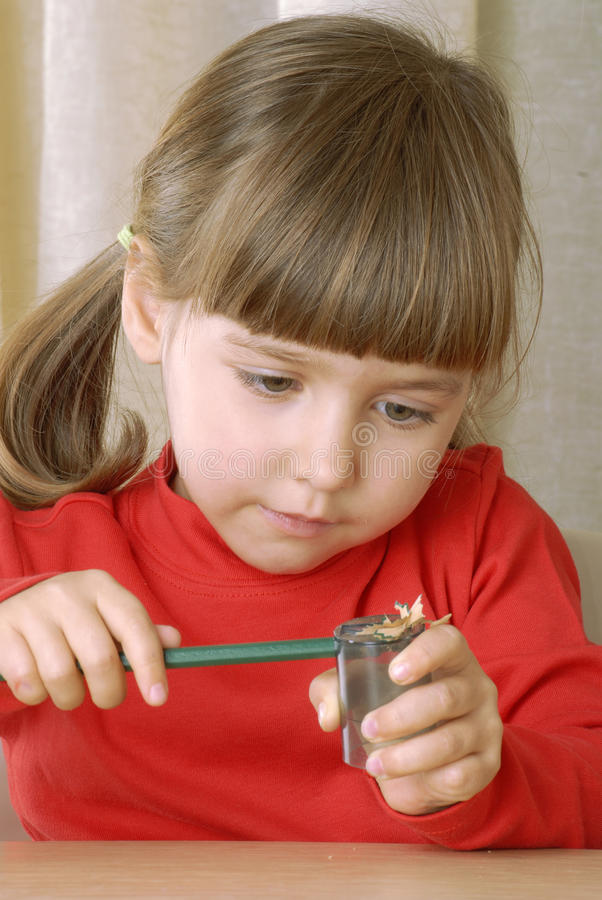 Ragazza bionda che affila una matita. immagini stock