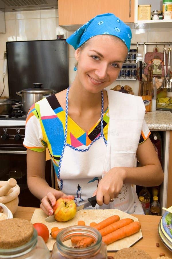 Ragazza bionda che cucina nella cucina fotografia stock libera da diritti