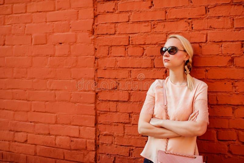 Ragazza bionda che posa vicino al muro di mattoni, posa pensierosa, fronte sensuale di bellezza, vetri scuri immagine stock libera da diritti