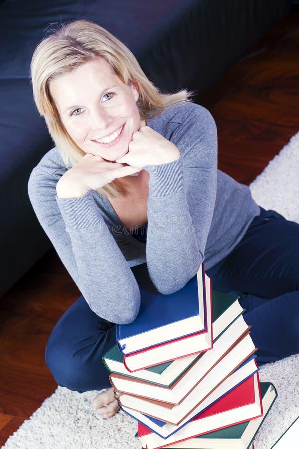 Ragazza bionda che si rilassa felicemente nei libri. fotografia stock libera da diritti