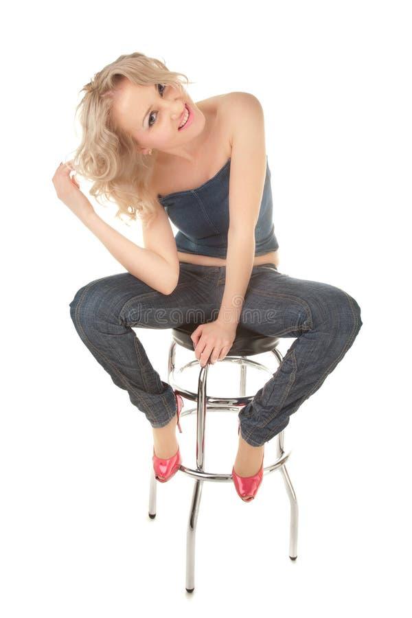 Ragazza bionda che si siede su una presidenza della barra fotografie stock libere da diritti