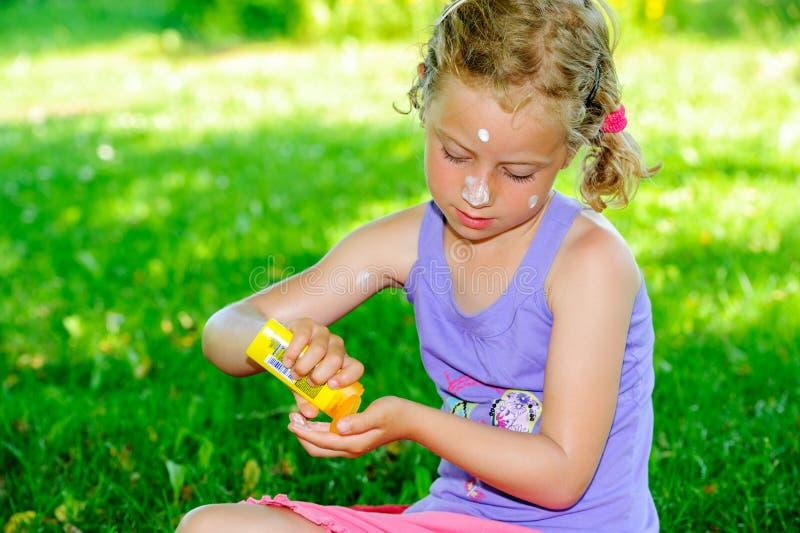 Ragazza bionda che utilizza la crema del sole nel giardino immagine stock libera da diritti