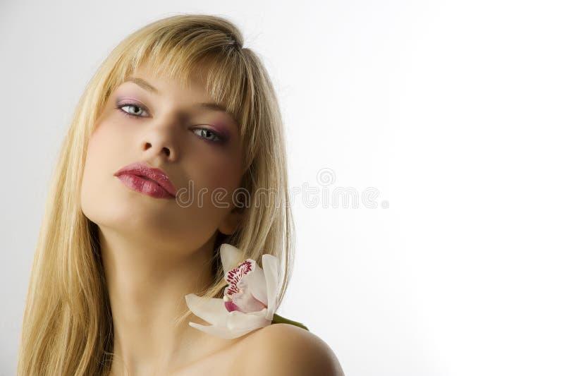Ragazza bionda con l'orchidea fotografia stock