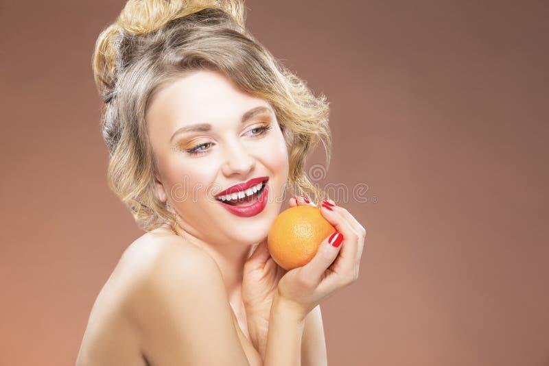 Ragazza bionda con una frutta arancio in mani Posando contro il fondo di colore fotografie stock
