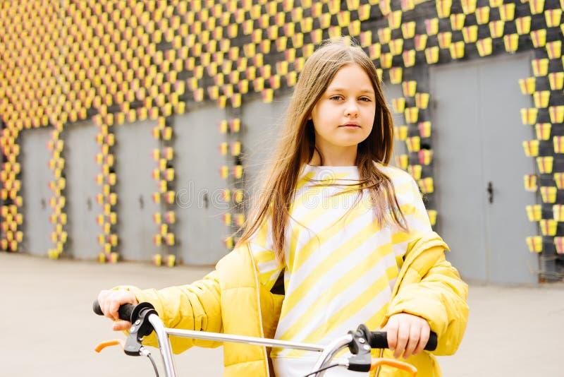Ragazza bionda dai capelli lunghi in un maglione giallo ed in un rivestimento giallo immagini stock