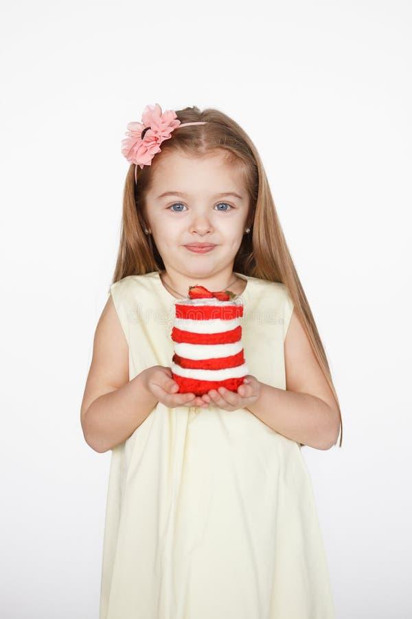 56a32cc85d Ragazza bionda del bambino che tiene un dolce rosso del velluto fotografie  stock libere da diritti