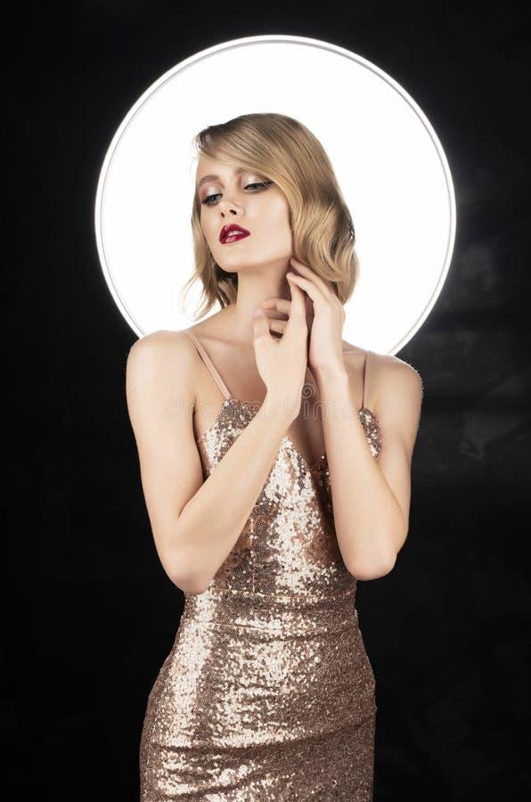 Ragazza bionda del fronte sveglio con le labbra rosse e l'acconciatura d'annata di stile, portanti un vestito scintillante dorato immagini stock libere da diritti