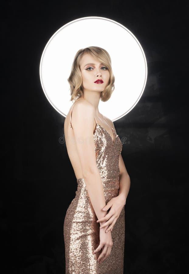 Ragazza bionda del fronte sveglio con le labbra rosse e l'acconciatura d'annata di stile, portanti un vestito scintillante dorato immagine stock