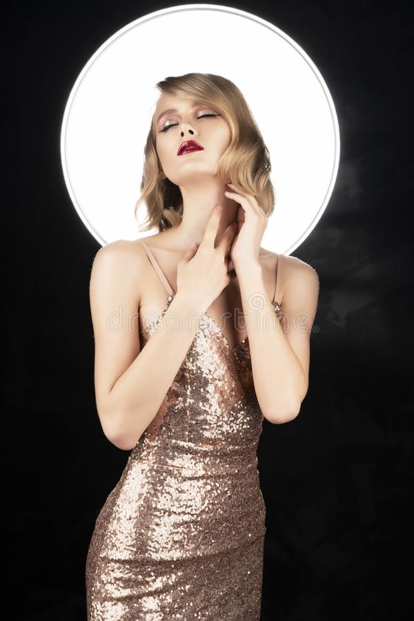 Ragazza bionda del fronte sveglio con le labbra rosse e l'acconciatura d'annata di stile, portanti un vestito scintillante dorato fotografia stock libera da diritti