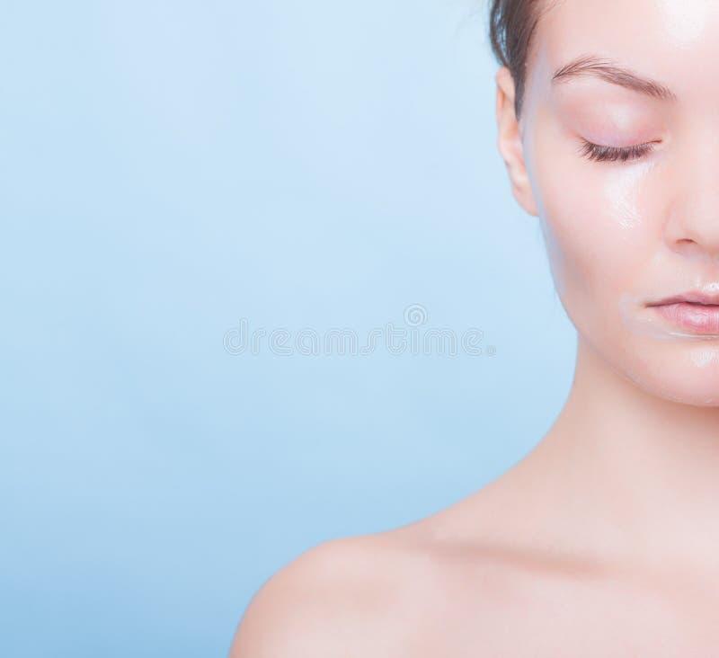 Ragazza bionda del ritratto nella maschera facciale sul blu. Fronte della parte. Bellezza e cura di pelle. fotografia stock