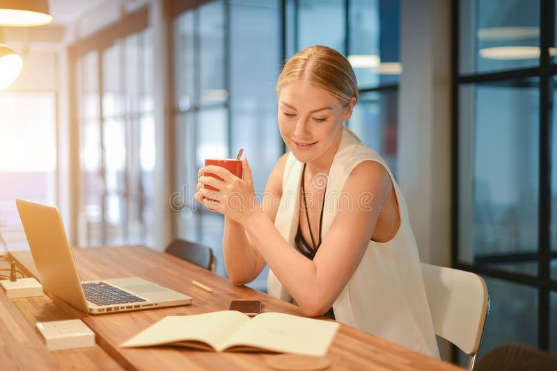 Ragazza bionda di affari che beve una tazza di caffè davanti ad un lapt fotografia stock