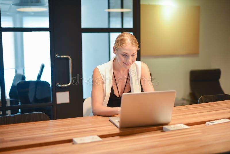 Ragazza bionda di affari che utilizza un computer portatile in un ufficio fotografia stock