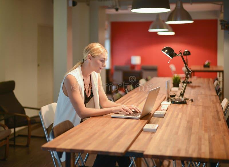 Ragazza bionda di affari che utilizza un computer portatile in un ufficio immagini stock libere da diritti