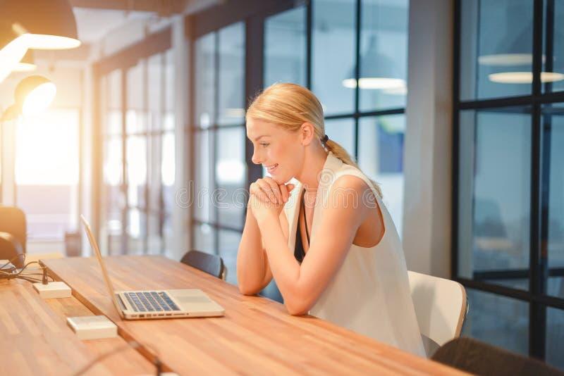 Ragazza bionda di affari felici che utilizza un computer portatile in un ufficio immagini stock