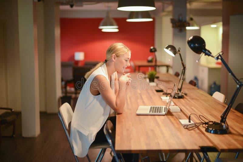Ragazza bionda di affari felici che utilizza un computer portatile in un ufficio fotografia stock libera da diritti