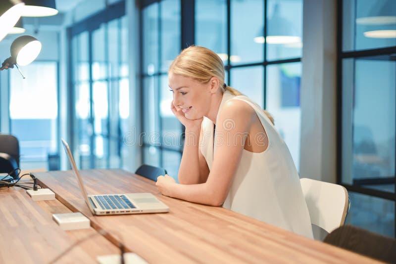 Ragazza bionda di affari felici che utilizza un computer portatile in un ufficio immagine stock libera da diritti