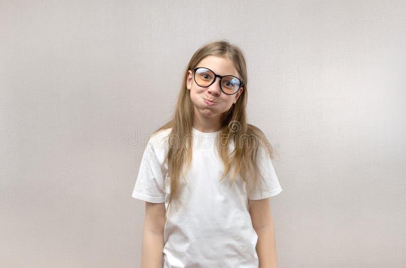 Ragazza bionda divertente in vetri che si contorcono il suo fronte, imitando, divertendosi Primo piano fotografia stock