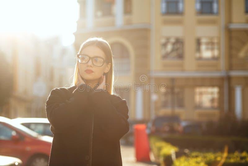 Ragazza bionda elegante con il cappotto d'uso dei capelli lunghi, posante nell'abbagliamento del sole Spazio vuoto fotografia stock