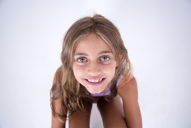 Ragazza bionda felice che esamina la macchina fotografica dalla parte anteriore fotografia stock