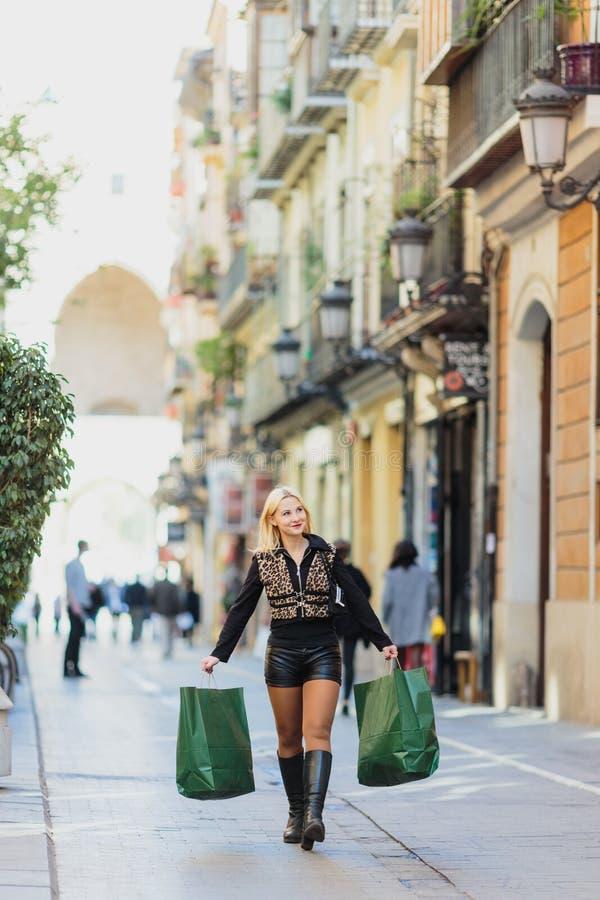 Ragazza bionda giovane bella di sogno felice che porta due pacchetti del Libro Verde fotografie stock