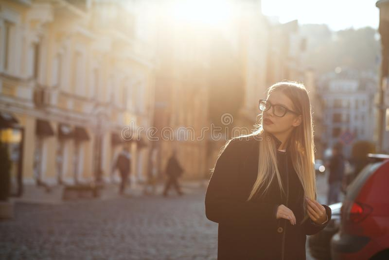 Ragazza bionda graziosa con il cappotto d'uso dei capelli lunghi, posante nell'abbagliamento del sole Spazio vuoto immagine stock