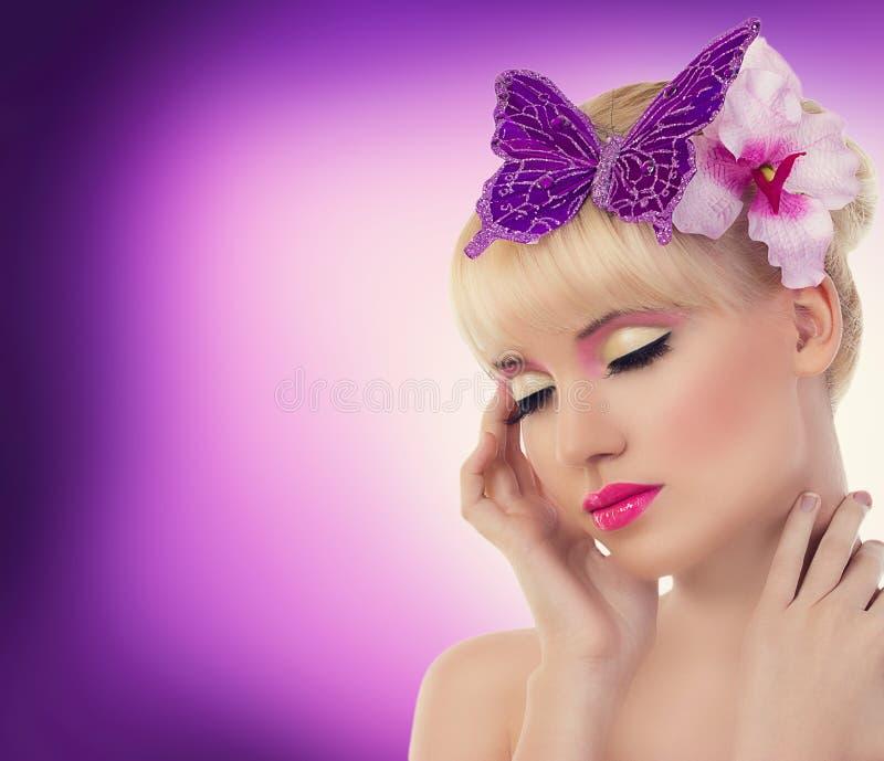 Ragazza bionda graziosa con il fiore e la farfalla dell'orchidea fotografia stock