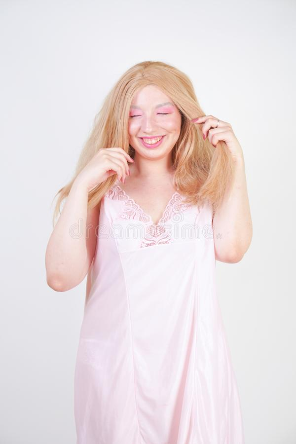Ragazza bionda paffuta incantante in mani graziose rosa di allungamento della camicia da notte su fondo bianco in studio immagine stock