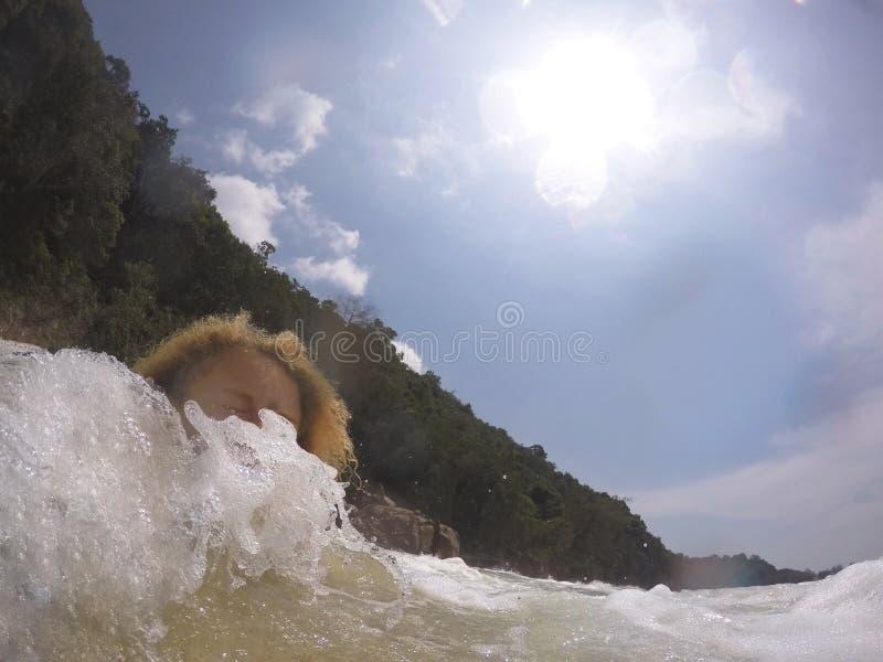 Ragazza bionda schiaffeggiata dall'onda immagini stock
