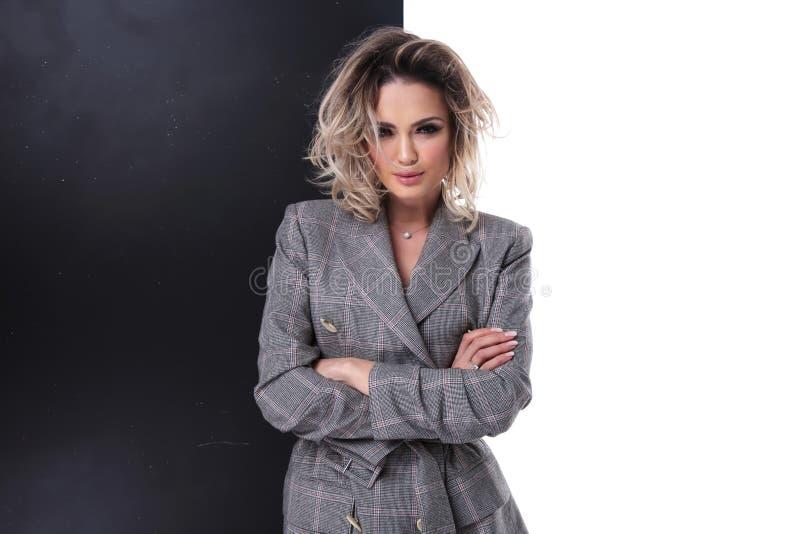 Ragazza bionda sexy che porta cappotto grigio con le sue armi attraversate fotografia stock libera da diritti