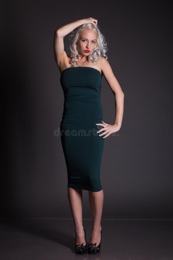 Ragazza bionda sexy in un vestito verde strettamente immagini stock
