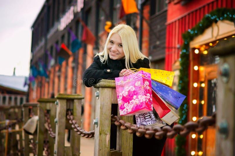 Ragazza bionda sorridente adorabile con i sacchetti della spesa immagine stock