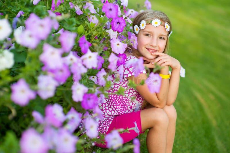 Ragazza bionda sorridente felice del bambino modello che si siede sull'erba in fiori immagine stock