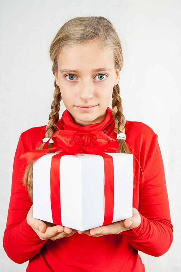 Ragazza bionda sveglia nel rosso con il contenitore di regalo fotografie stock libere da diritti