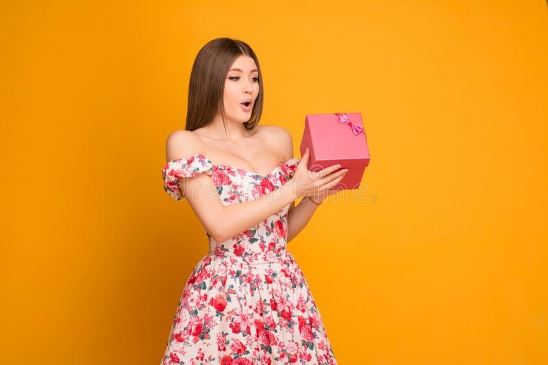 Ragazza bionda in un vestito che tiene un contenitore di regalo in sue mani immagine stock