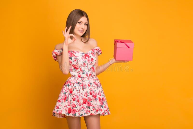 Ragazza bionda in un vestito che tiene un contenitore di regalo in sue mani fotografia stock