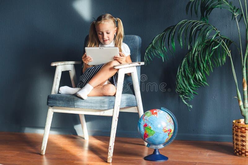 Ragazza blondy sorridente graziosa che si rilassa su una sedia vicino al globo all'interno a casa con un pc della compressa in su immagini stock