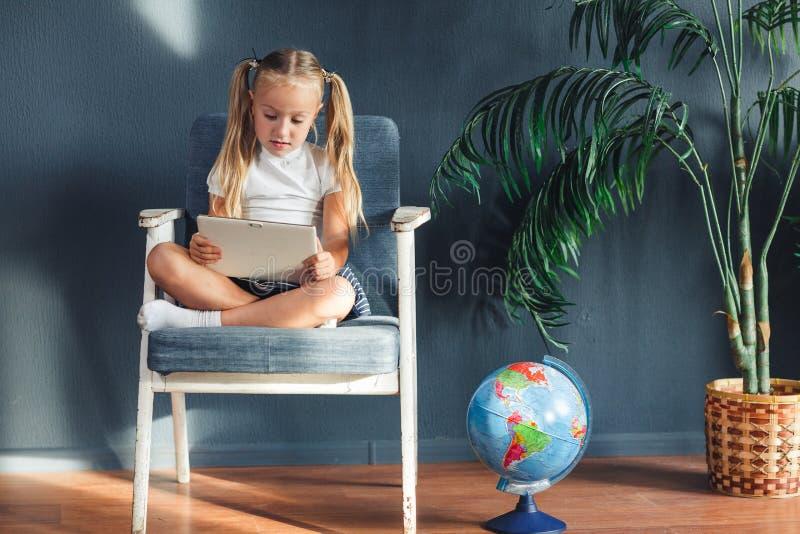 Ragazza blondy sorridente graziosa che si rilassa su una sedia vicino al globo all'interno a casa con un pc della compressa in su fotografia stock