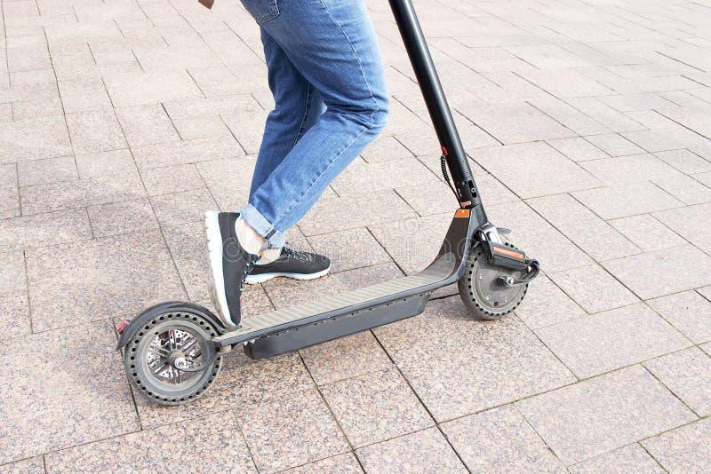 Ragazza in blue jeans che guidano un motorino elettrico Elettro motorino di trasporto ecologico tecnologico Stile di vita attivo  immagine stock