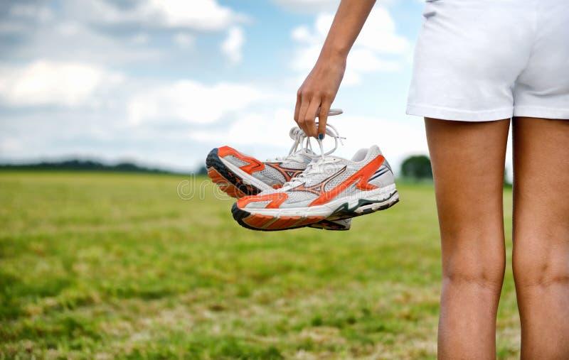 Ragazza in breve che tengono le sue scarpe da tennis fotografie stock libere da diritti