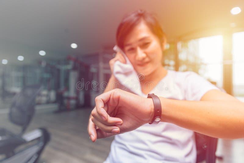 Ragazza in buona salute che guarda il braccialetto astuto di salute dell'inseguitore di forma fisica fotografie stock libere da diritti