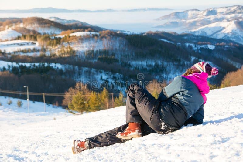 Ragazza caduta giù sulla neve fotografia stock