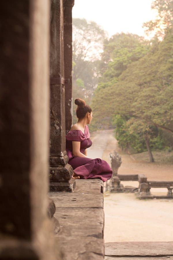 Ragazza cambogiana in vestito khmer che guarda l'alba a Angkor Wat fotografia stock libera da diritti