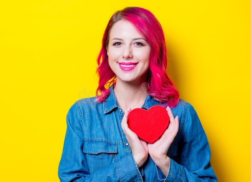 Ragazza in camicia blu che tiene una scatola rossa di forma del cuore immagini stock libere da diritti