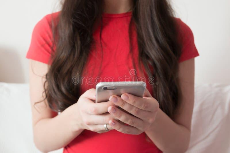 Ragazza in camicia rossa che manda un sms sullo Smart Phone fotografia stock