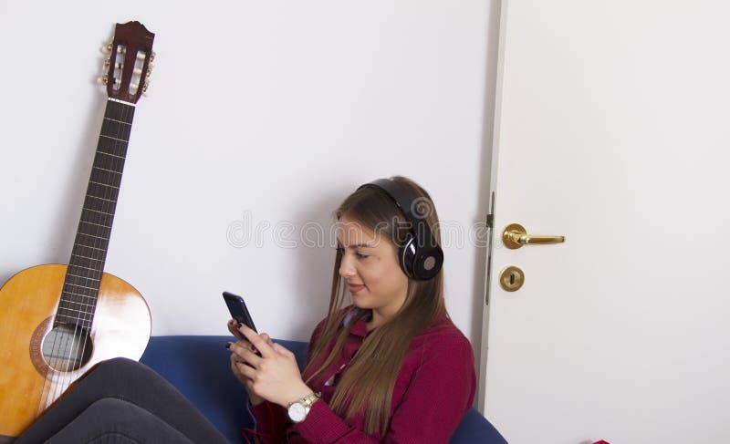 ragazza in camicia rossa Giudica mobile ed ascolta musica immagine stock libera da diritti
