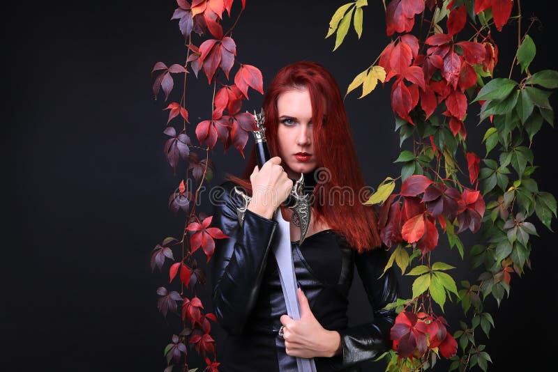 Ragazza capa di rosso fra le foglie che tengono una spada immagine stock