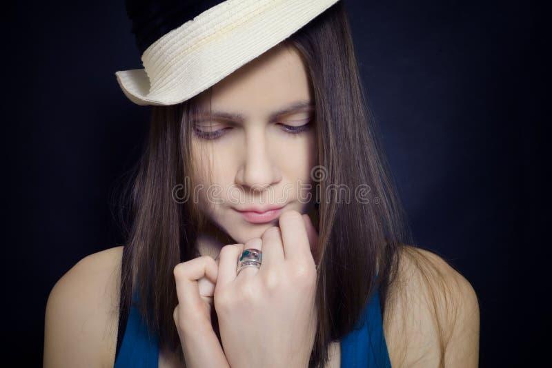 Ragazza in cappello bianco su priorità bassa nera immagine stock
