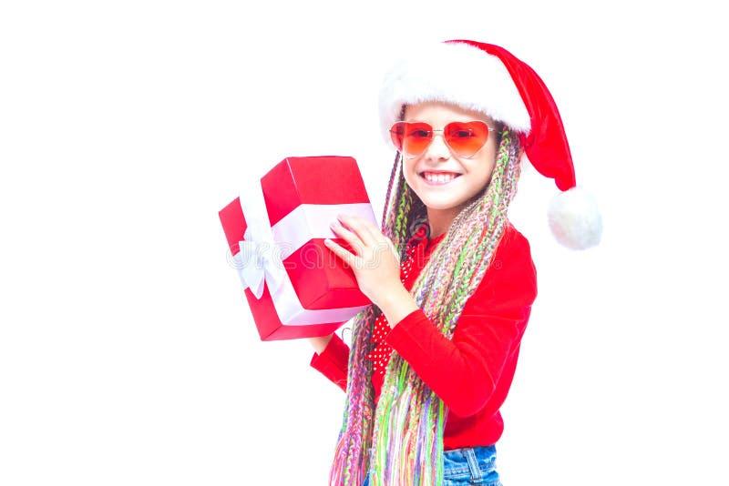 Ragazza in cappello del ` s di Santa Il ritratto di piccola scatola sveglia della tenuta della ragazza di regalo di Natale, picco immagine stock libera da diritti