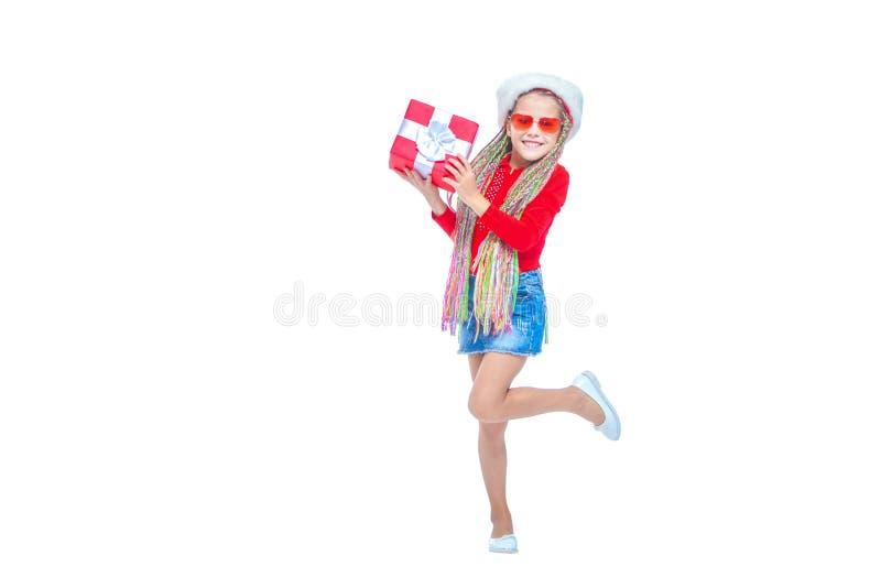 Ragazza in cappello del ` s di Santa Il ritratto di piccola scatola sveglia della tenuta della ragazza di regalo di Natale, picco fotografia stock libera da diritti